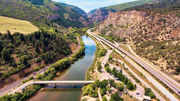 Antena kanionu majestatycznych gór skalistych z torami autostradowymi i kolejowymi
