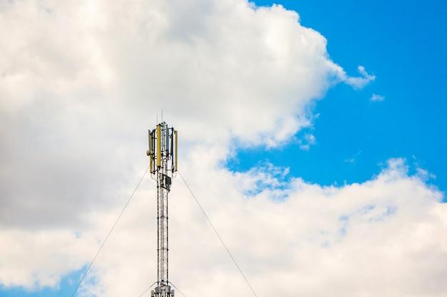 Antena komunikacji komórkowej na tle białych chmur, transfer informacji na odległość
