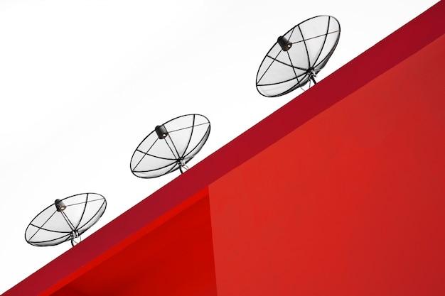Antena satelitarna na dachu czerwonego budynku.