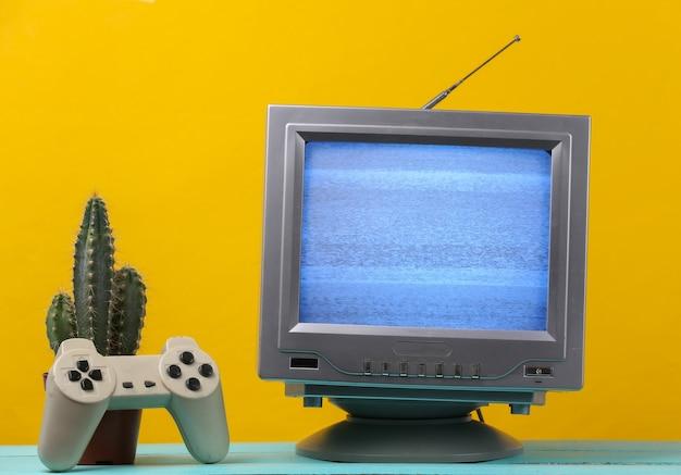 Antena staromodny odbiornik telewizyjny w stylu retro z gamepadem, kaktus na żółto.