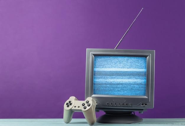 Antena staromodny odbiornik telewizyjny w stylu retro z gamepadem na fioletowo.