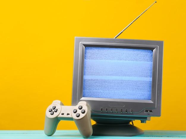 Antena staromodny odbiornik telewizyjny w stylu retro z gamepadem na żółto.