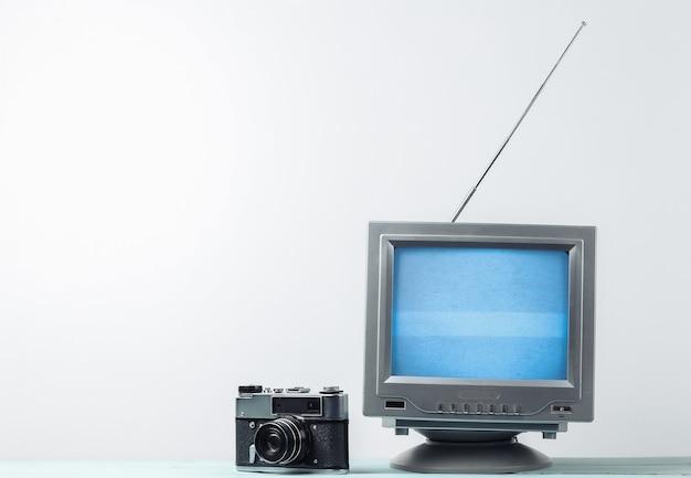 Antena staromodny odbiornik tv retro i kamera filmowa na białej ścianie
