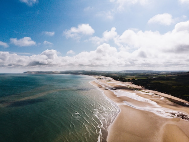 Antena strzał piękny plażowy brzeg blisko trawiastego pola z chmurnym niebem