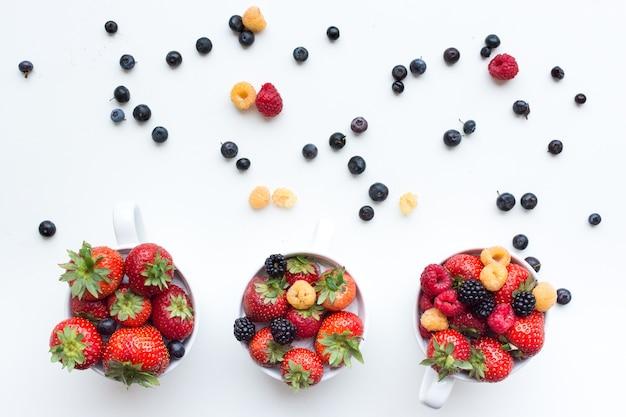 Antena strzelająca kolorowe zdrowe świeże jagody w filiżankach na białym tle
