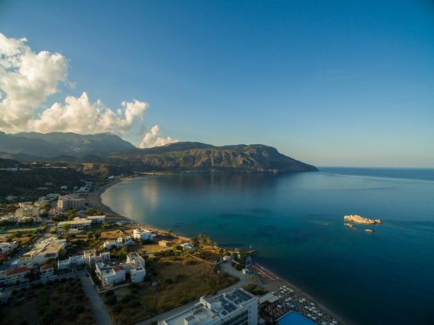 Antena strzelał domy na plaży pięknym spokojnym oceanem chwytającym w karpathos, grecja