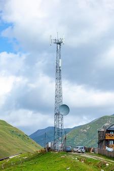 Antena telefoniczna, błękitne niebo i białe chmury w uszguli, swanetia, gruzja. telekomunikacja.