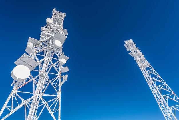 Antena telekomunikacyjna. pokryta lodem wieża komórkowa na dachu stacji bazowej znajdującej się na wyżynach. niebieskie niebo.