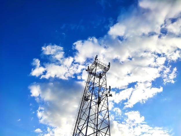 Antena wieży telekomunikacyjnej na niebieskim zachmurzonym niebie
