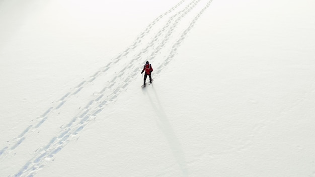 Antena zima w rakietach śnieżnych całej dolinie na zachód słońca. zapierający dech w piersiach naturalny krajobraz. aktywna grupa ludzi w zimowe ubrania na rakietach śnieżnych na snowy jeziora. podróżni w rakietach śnieżnych odkrywają okolicę