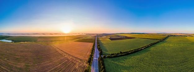Antenowe drone panorama widok natury w mołdawii o zachodzie słońca. dym z ogniska, szerokie pola, droga, słońce