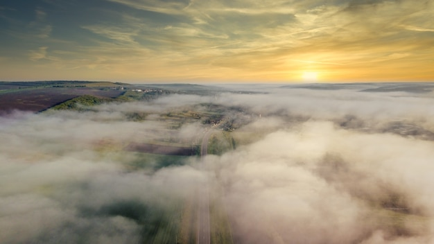 Antenowe drone widok natury w mołdawii w godzinach porannych. pola i niskie wzgórza, wioska z mgłą w powietrzu