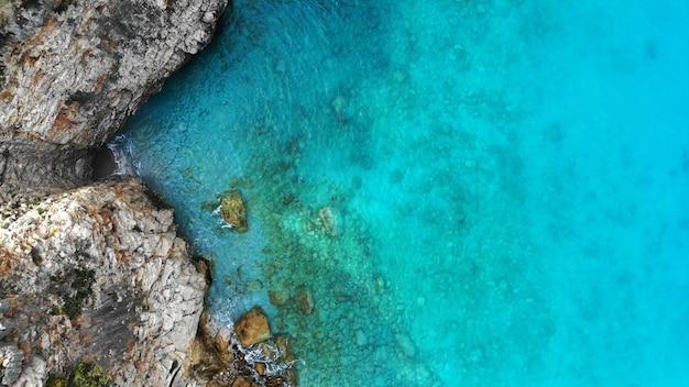 Antenowy. woda morska i brzeg skały tekstura tło. widok z góry z drona.