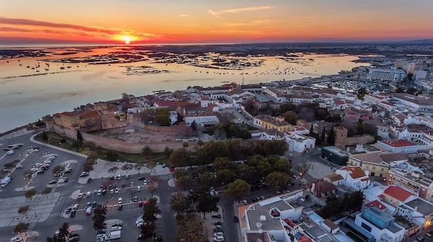 Antenowy. zachód słońca nad starym miastem w faro, widok z powietrza, portugalia