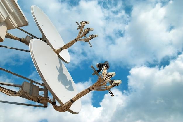 Anteny satelitarne poszukujące sygnału na błękitnym niebie