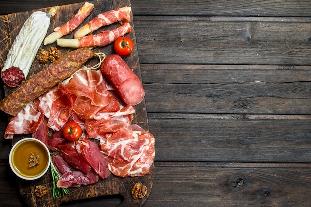 Antipasto. asortyment przekąsek mięsnych na pokładzie. na drewnianym.