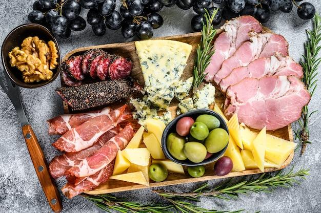 Antipasto różne przystawki, deska do krojenia z prosciutto, salami, coppa, serem i oliwkami. szare tło. widok z góry
