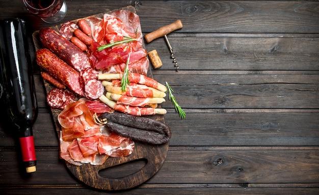 Antipasto.różny asortyment przekąsek mięsnych z dodatkiem czerwonego wina. na drewnianym.