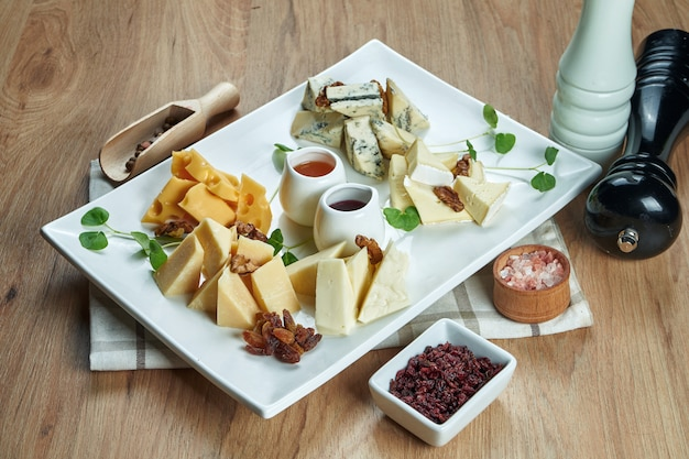 Antipasto - talerz serowy. różne domowe sery na talerzu ceramicznym - brie, camembert, holenderski z miodem i orzechami. przystawka do wina. widok z góry jedzenie