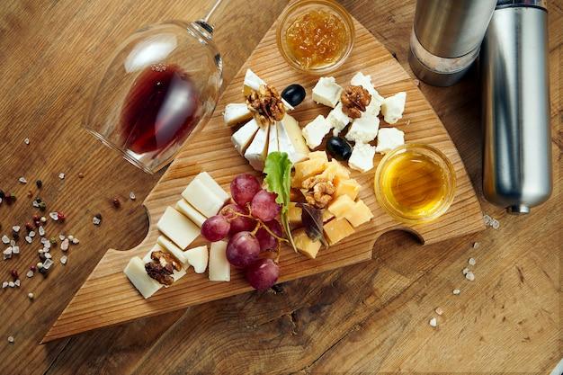 Antipasto - talerz serowy. różne domowe sery na talerzu ceramicznym - brie, camembert, holenderski z miodem i orzechami. przystawka do wina. widok z góry, leżał płasko, miejsce