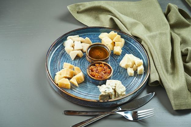 Antipasto - talerz serowy. różne domowe sery na talerzu ceramicznym - brie, camembert, holenderski z miodem i orzechami. przystawka do wina.