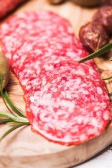 Antipasto z salami i zielone oliwki na desce oliwnej