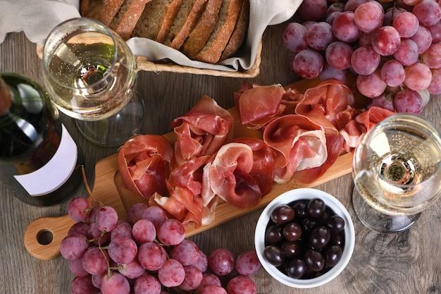 Antipasto. zestaw do wina z suszoną szynką jamon z winogronami i oliwkami