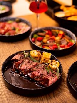 Antrykot wołowina grillowany stek z płomieniami ognia na desce do krojenia z rozmarynem, pieprzem i solą. grillowane warzywa, kukurydza. mistrz kuchni gotowania pysznego grilla z grilla.