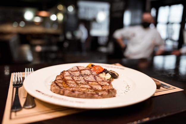 Antrykot wołowy grillowany stek z gałązką rozmarynu, pieprzem i solą. grillowane warzywa na białym talerzu w restauracji. mistrz kuchni gotuje pyszne grillowe warzywa z grilla.