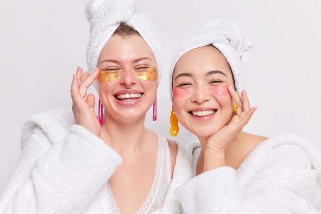 Anty starzenie się i koncepcja zabiegów na twarz. radosne, różnorodne młode kobiety cieszą się zabiegami upiększającymi w domu, redukują obrzęki dzięki hydrożelowym plastrom