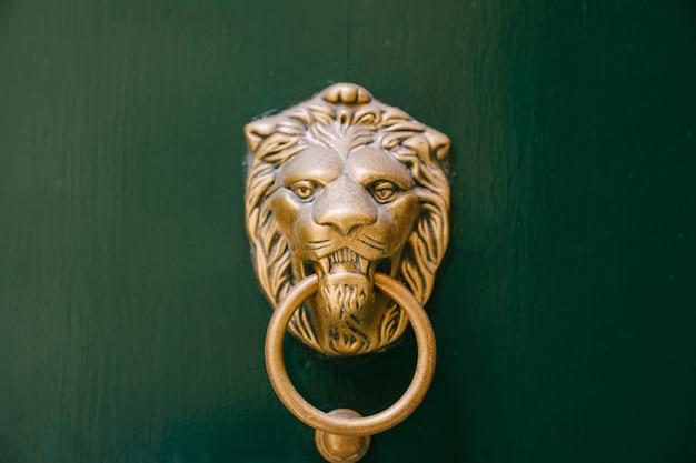 Antyczna klamka na zielonych drewnianych drzwiach w kształcie twarzy lwa z pukaniem w in
