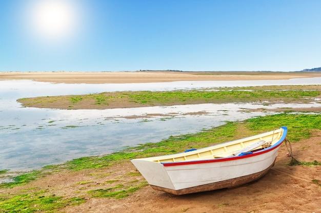 Antyczna łódź rybacka na dennym przypływie.