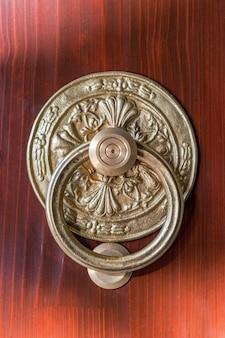 Antyczna okrągła gałka z brązu z kołatką na drewnianych drzwiach