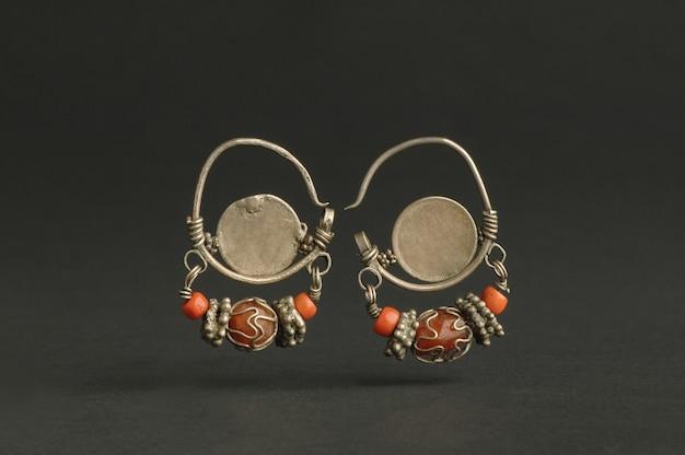 Antyczne antyczne kolczyki z kamieniami na czarnym tle. biżuteria w stylu vintage z azji środkowej!