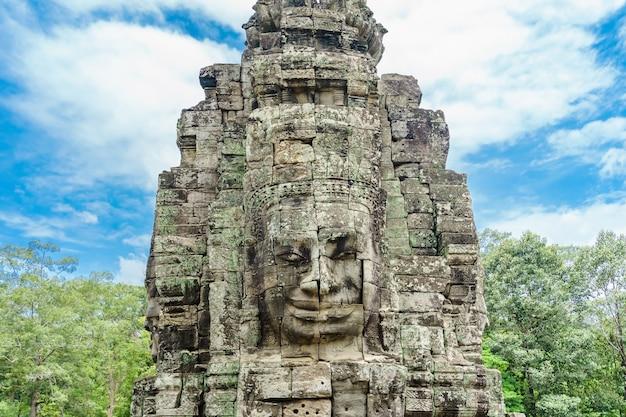 Antyczne kamień twarze przy niebieskim niebem chmurnym bayon świątynia, angkor wat, siam przeprowadzają żniwa, kambodża.