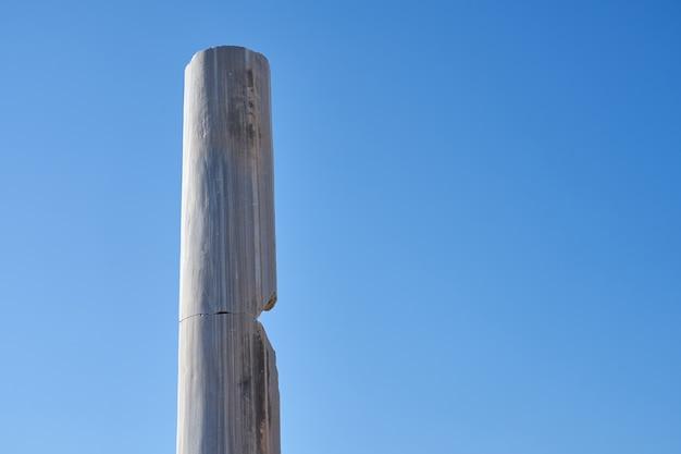 Antyczne kamienne kolumny na tle jasnego nieba.