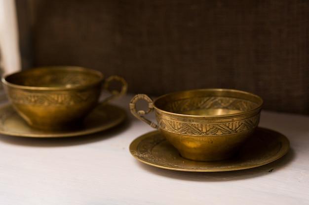 Antyczne kubki do herbaty z miedzianymi spodkami. niezwykłe elementy wystroju domu