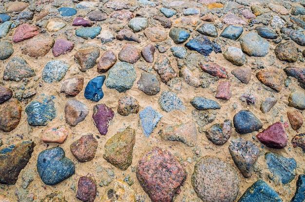 Antyczni brukowi kamienie w rzadkich kamieniach w piasku.