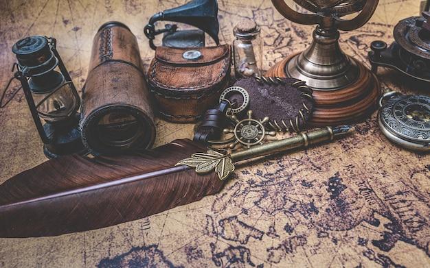 Antyczny brąz pióro pióro i stara kolekcja na starej mapie świata