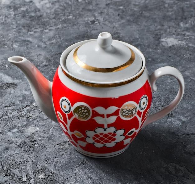 Antyczny ceramiczny czajniczek zbliżenie z wzorami na czarny betonowy stół.