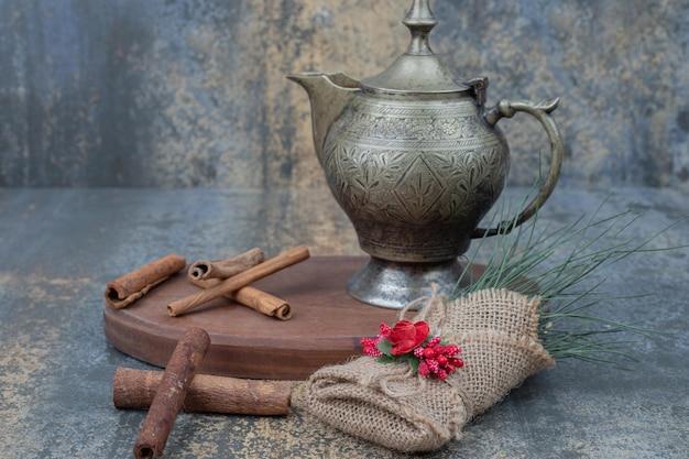 Antyczny czajnik z cynamonem na drewnianym talerzu.