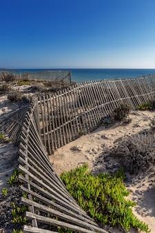 Antyczny drewniany ogrodzenie na tle morze plaża. portugalia algarve.