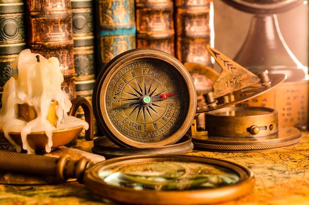 Antyczny kompas na tle kuli ziemskiej i książek. zabytkowy styl. 1565 stara mapa roku.