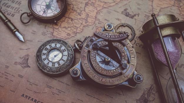 Antyczny kompas z brązu z kolekcji piratów na starej mapie świata