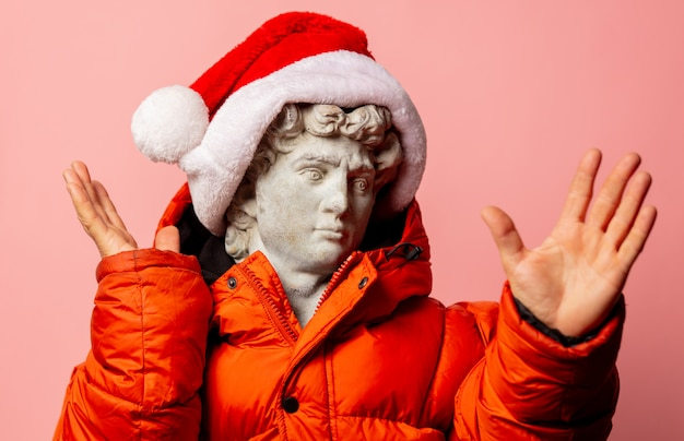 Antyczny posąg ubrany w kurtkę puchową i czapkę mikołaja na różowej ścianie