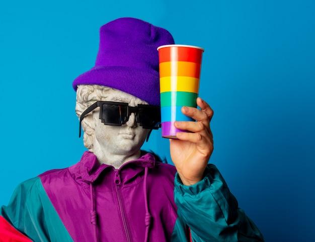 Antyczny posąg ubrany w modne ubrania z lat dziewięćdziesiątych trzyma kubek napoju