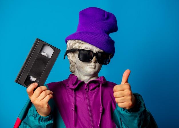 Antyczny posąg ubrany w modne ubrania z lat dziewięćdziesiątych zawiera kasetę vhs