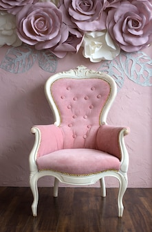 Antyczny różowy fotel z elementami białego drewna stoi przy różowej ścianie ozdobionej różami