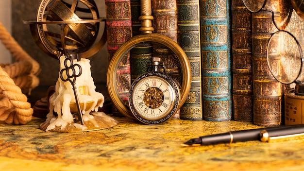 Antyczny zegar na tle szkła powiększającego i książek. zabytkowy styl. 1565 stara mapa roku.