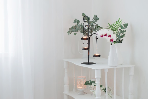 Antykwarski świecznik z płonącymi świeczkami i kwiatami na białej starej drewnianej półce